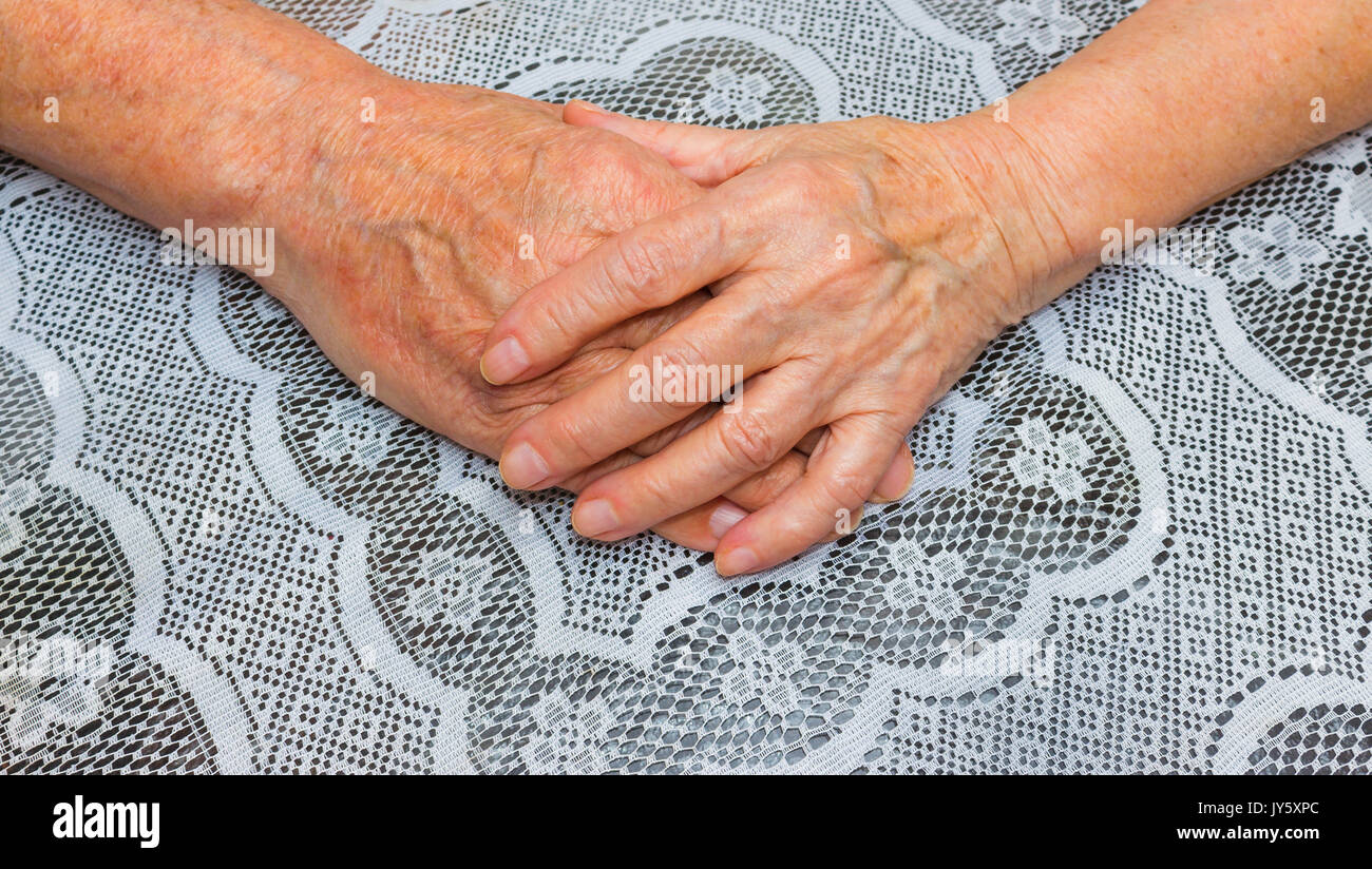 Hands of two loving senior people on a tablecloth background - Stock Image