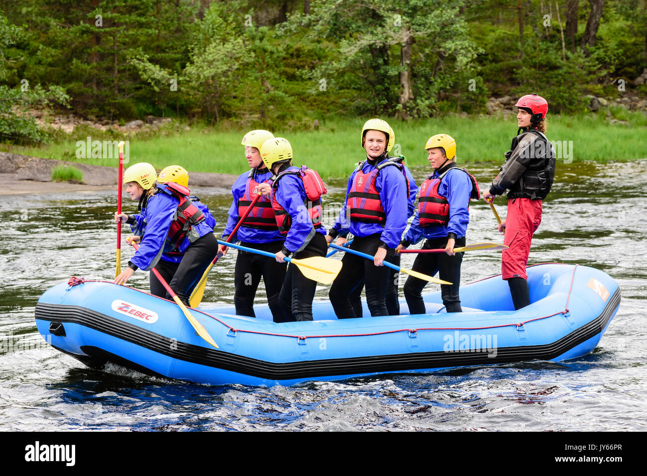 Byglandsfjord, Norway - August 1, 2017: Travel documentary of rafting group having an adventure on the river. Group standing in boat while in calm wat - Stock Image