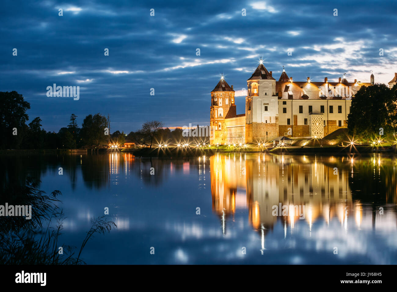 Mir, Belarus. Mir Castle Complex In Bright Evening Illumination With Glow Reflections On Lake Water. Famous Landmark, Ancient Gothic Monument Of Feuda - Stock Image