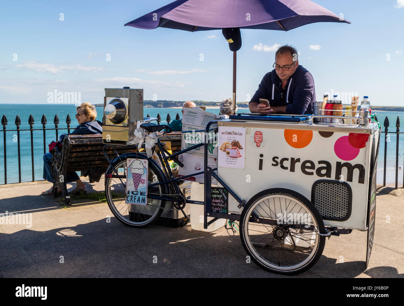 A man selling ice cream from a bicycle on the sea front in Tenby, Wales - Stock Image