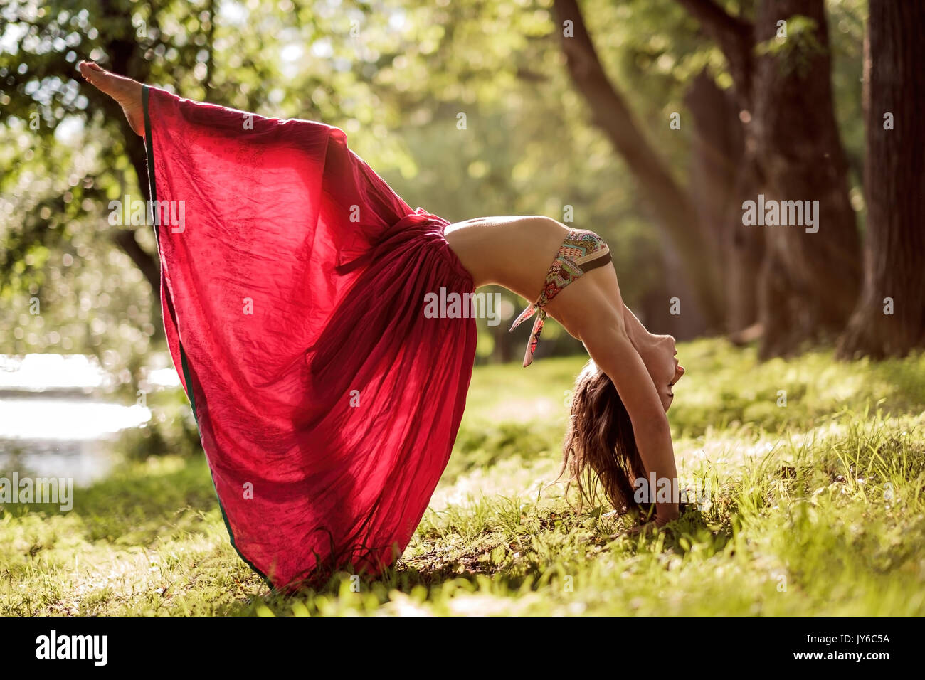 Fit young beautiful woman wearing red skirt working out outdoors in park on summer day, doing Bridge Pose from yoga Stock Photo