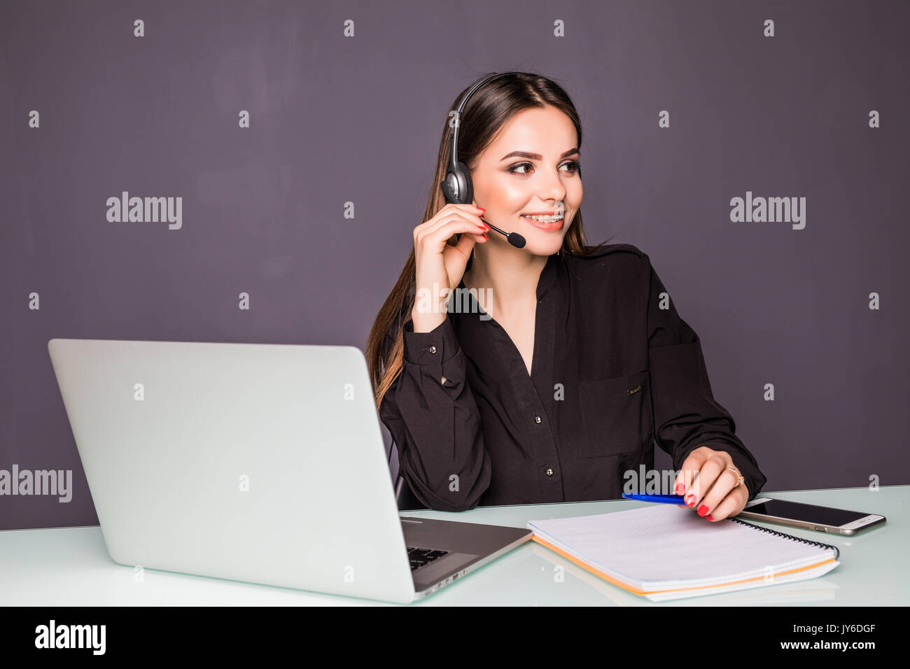 Portrait of beautiful business woman working at her desk with headset and laptop Stock Photo