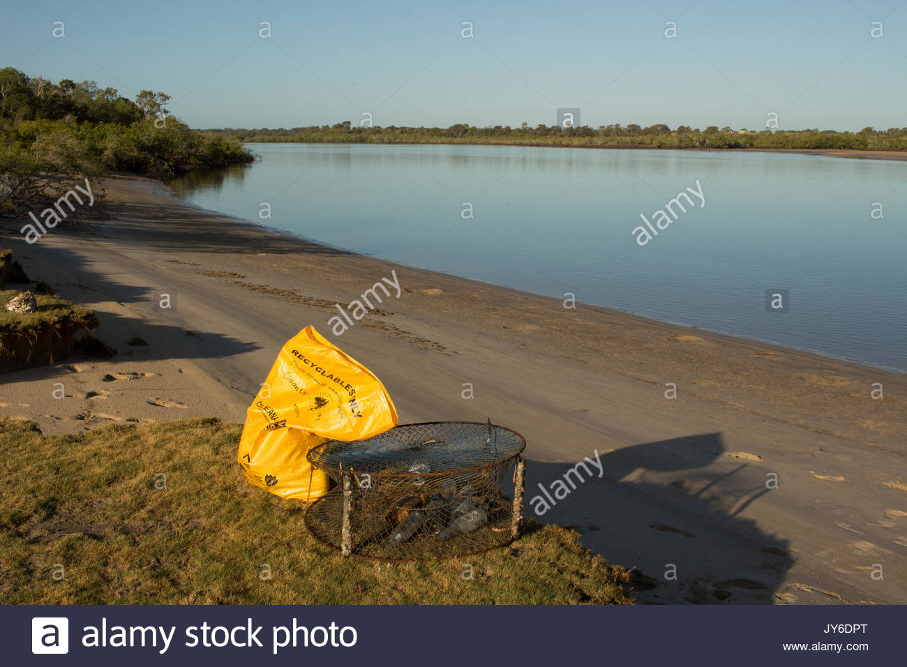 A bag and other collected garbage beside the Elliott River in Queensland, Australia. Clean Up Australia Day is an annual nation wide voluntary litter  - Stock Image