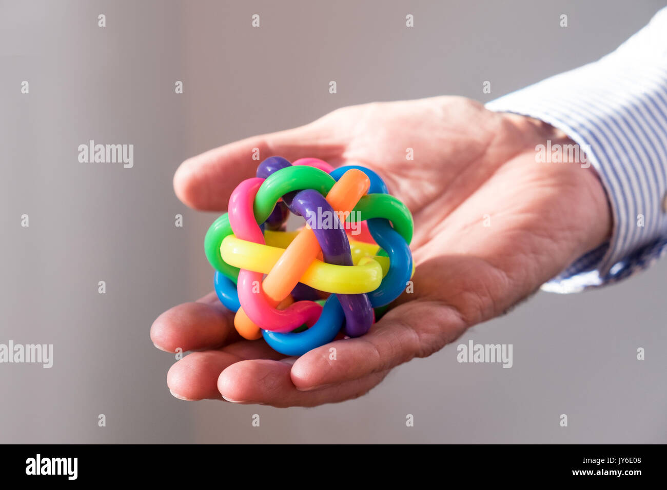 Hand holding out  ball made of different colors - Stock Image