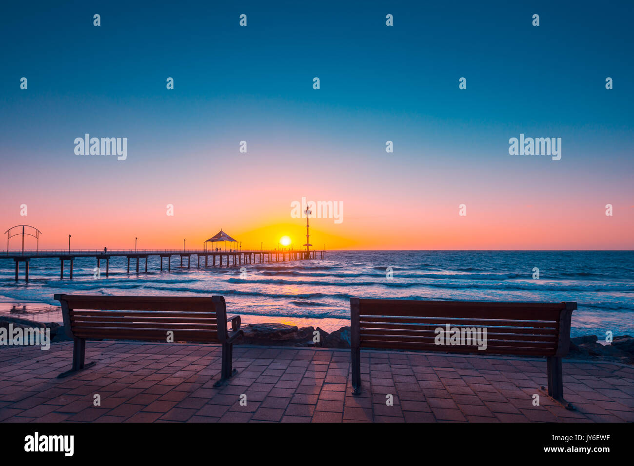 Brighton Beach view with people walking along jetty at sunset, South Australia - Stock Image