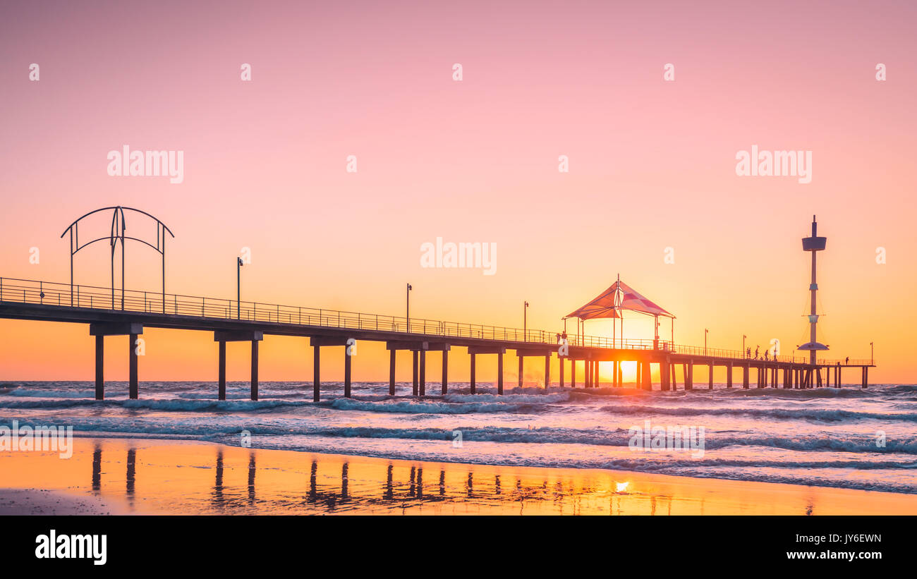 People walking along Brighton Beach jetty at sunset, South Australia - Stock Image