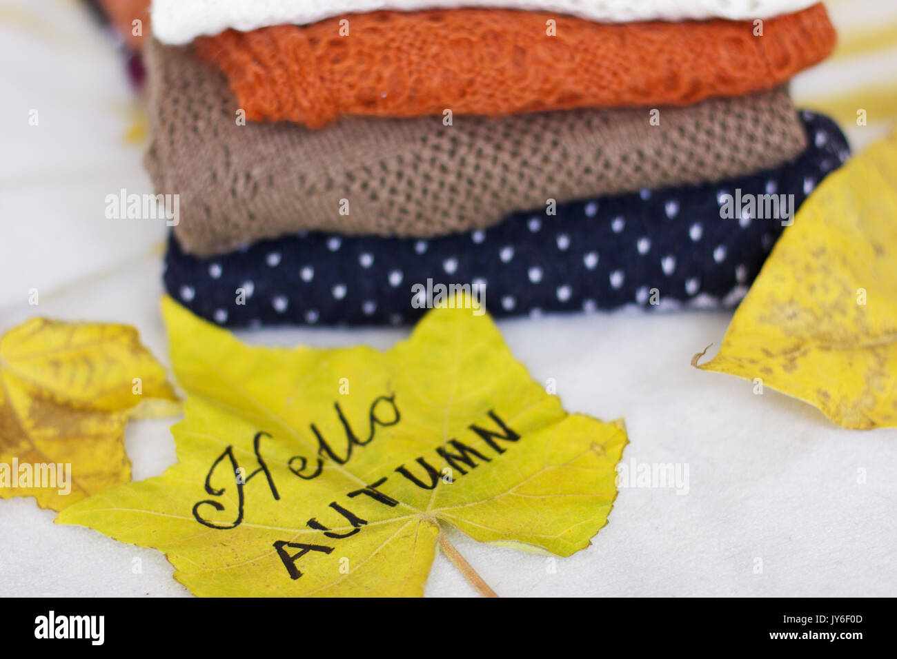 A Pile Of The Warm Sweaters And A Yellow Maple Leaf   Stock Image