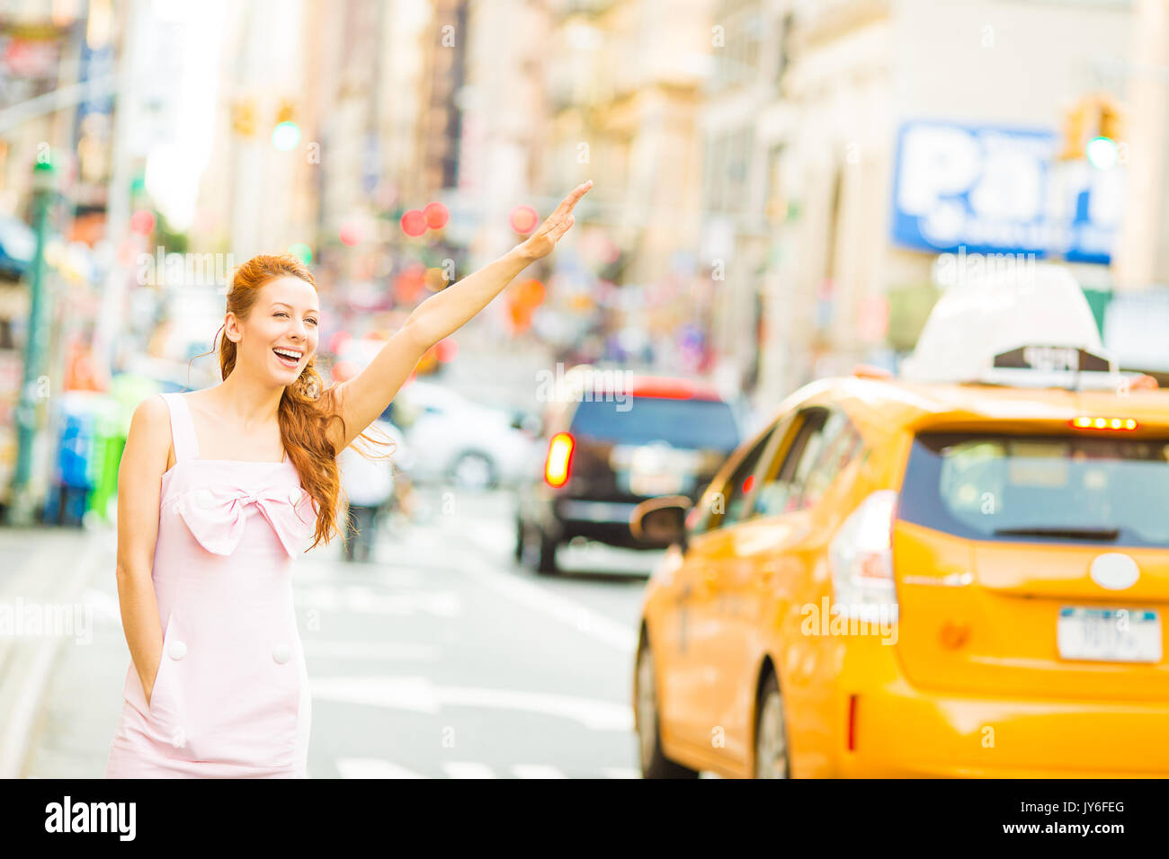 A young woman hailing a yellow taxi cab while walking on a street in New York city Stock Photo