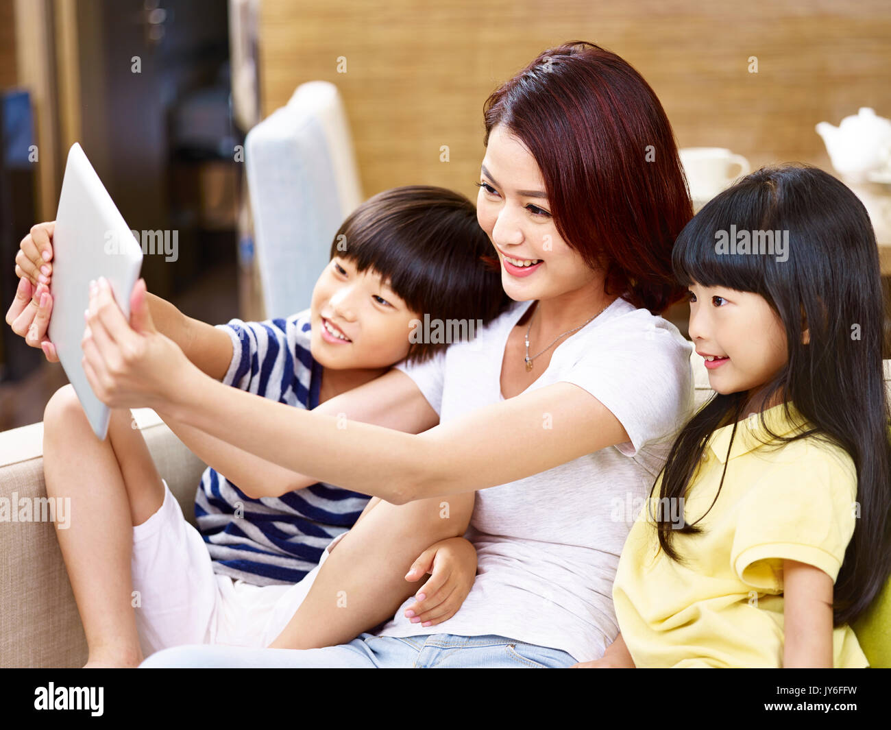 young asian mother and children sitting on sofa taking a selfie with digital tablet, happy and smiling. - Stock Image