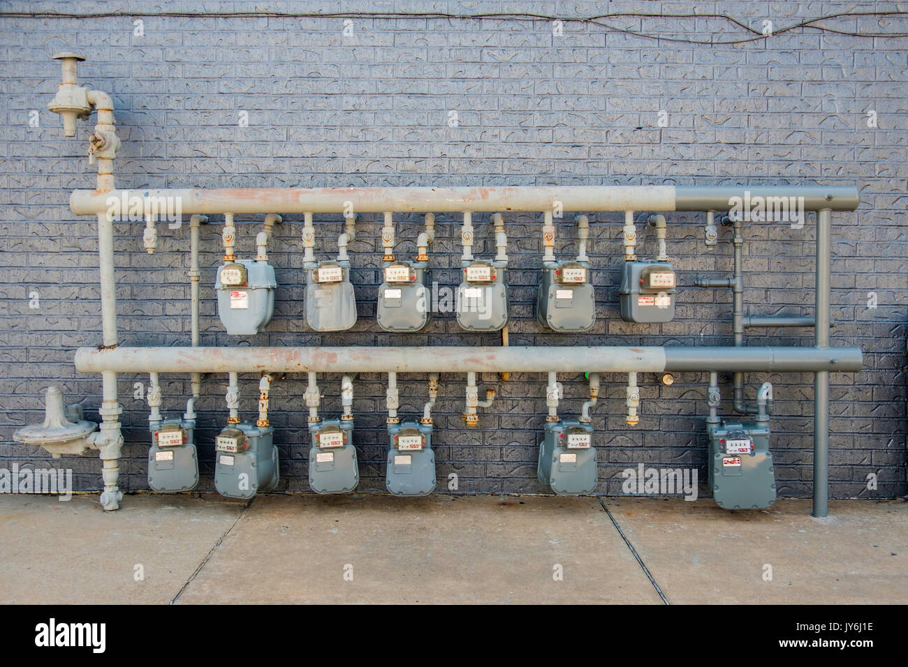 An array of natural gas meters metering gas usage by individual consumers behind a building in a strip mall. Norman, Oklahoma, USA. - Stock Image