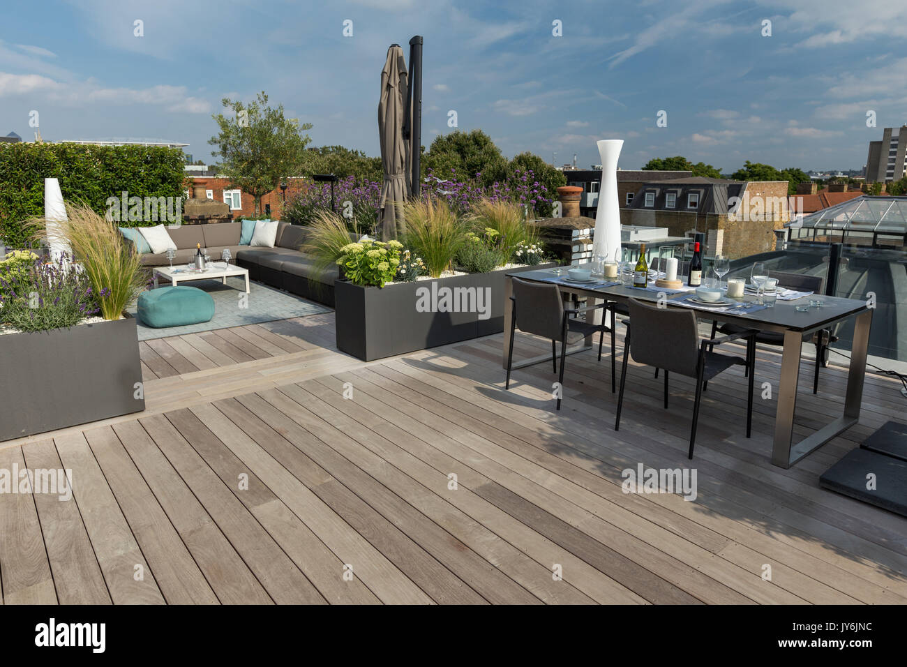 Luxurious roof terrace in london with hardwood timber decking contemporary planters with lush planting and modern outdoor furniture