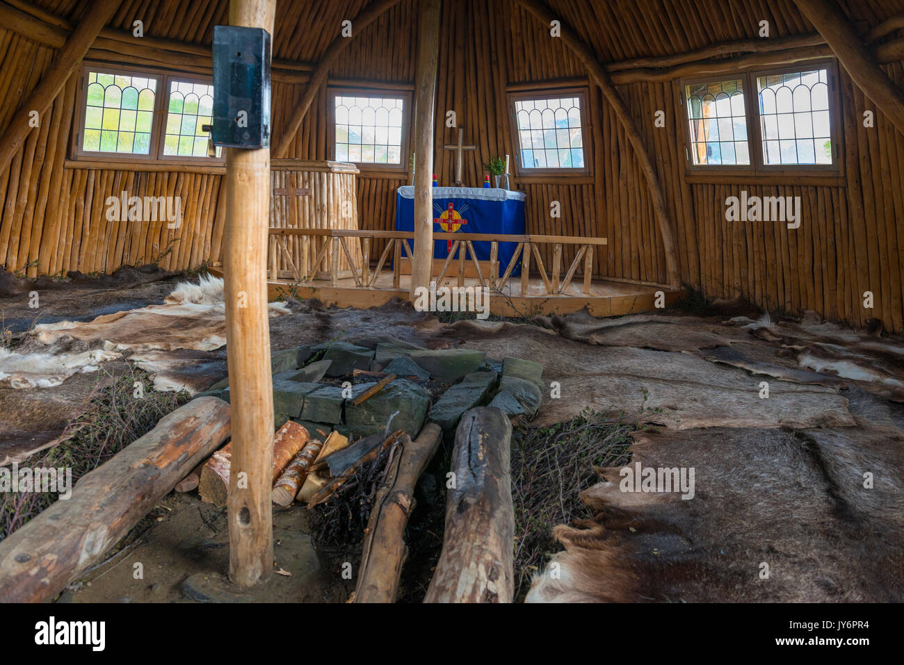 Interior of a Sami church goahti in Staloluokta in Swedish Lapland. The floor is covered with reindeer fur, and there is a fireplace. - Stock Image