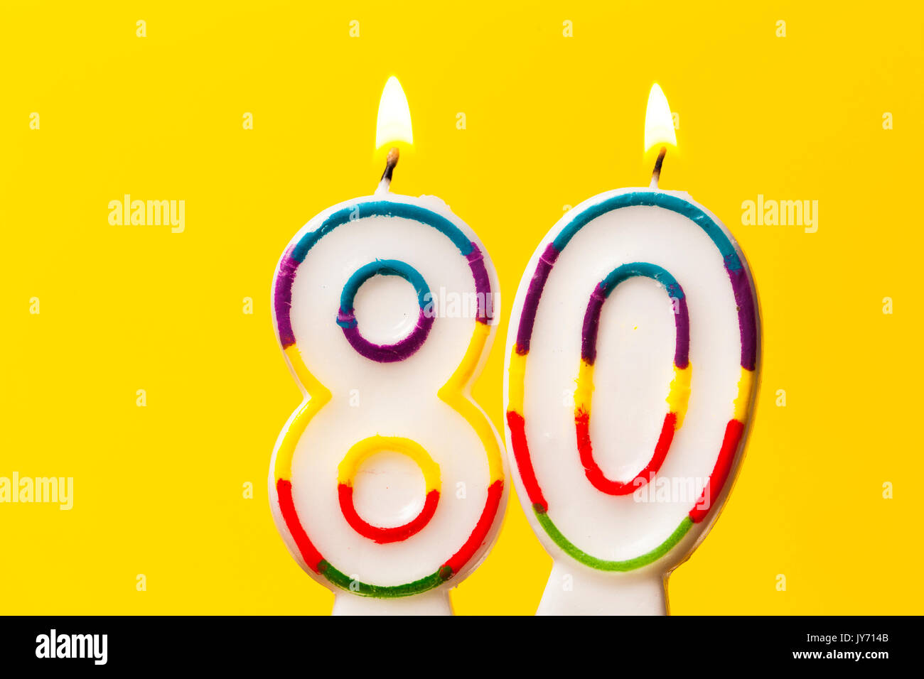 Number 80 Birthday Celebration Candle Against A Bright Yellow Background