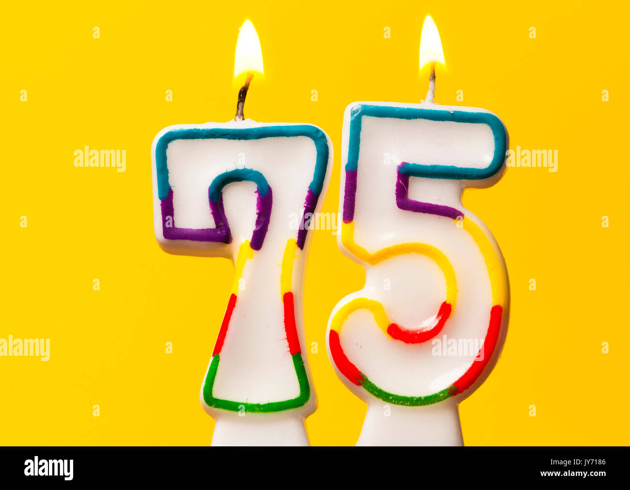 Number 75 Birthday Celebration Candle Against A Bright Yellow Background