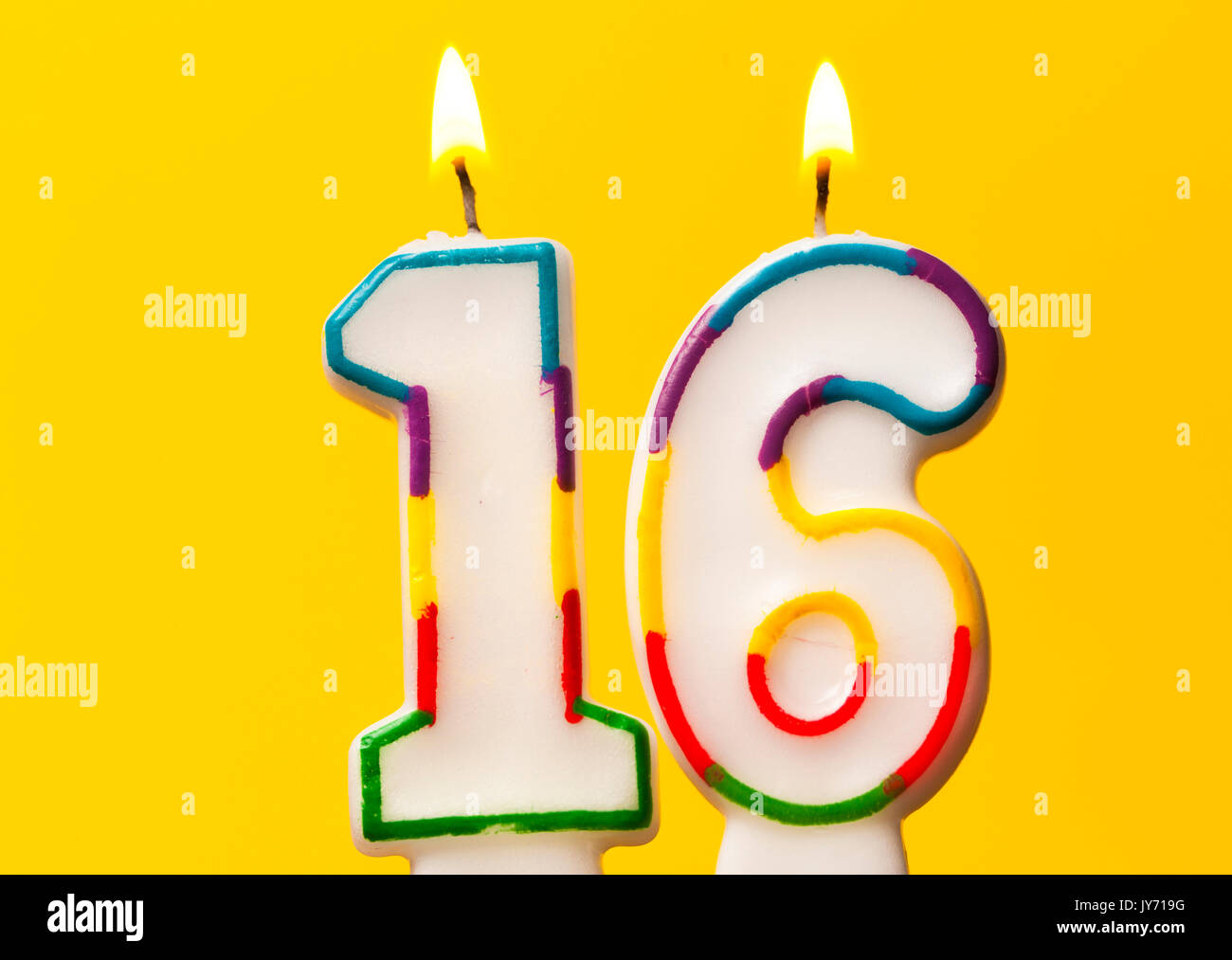 Number 16 Birthday Celebration Candle Against A Bright Yellow Background