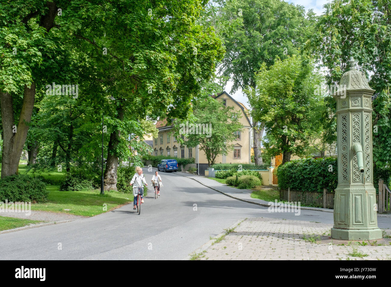 Bikers at Djurgarden  in Stockholm. Djurgarden is a recreational area with historical buildings, monuments, amusement park and open-air museum. - Stock Image
