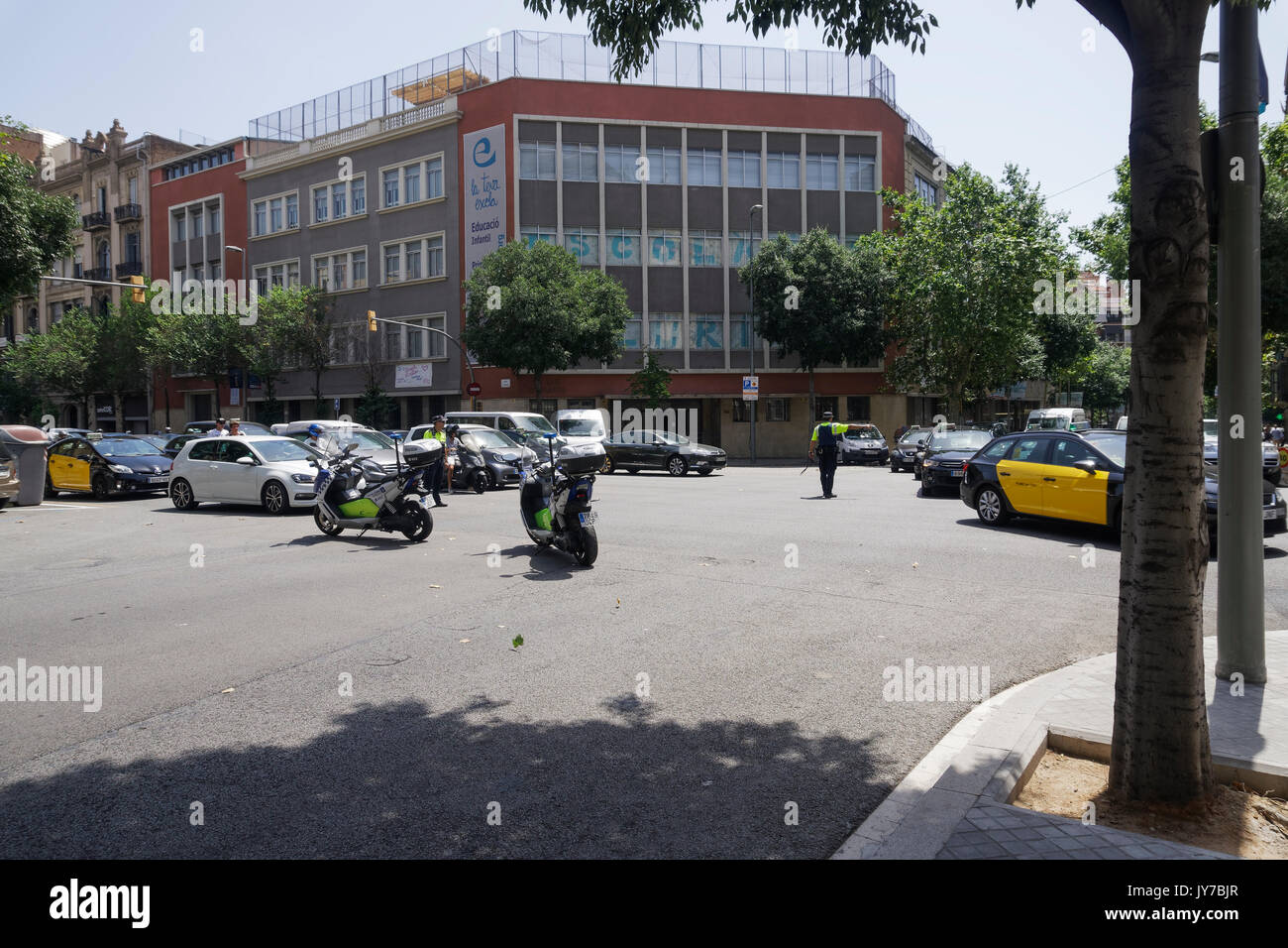 Police men of Guardia Urbana securing road safety on Barcelona city center. - Stock Image