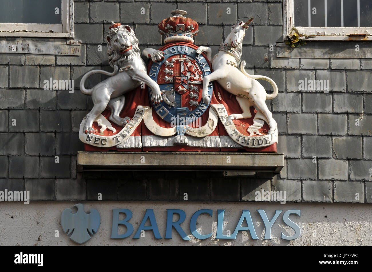 The Barclays Bank emblem and sign with the name of the bank over a door with a coat of arms or insignia emblem. Financial institutions and fiscal. - Stock Image