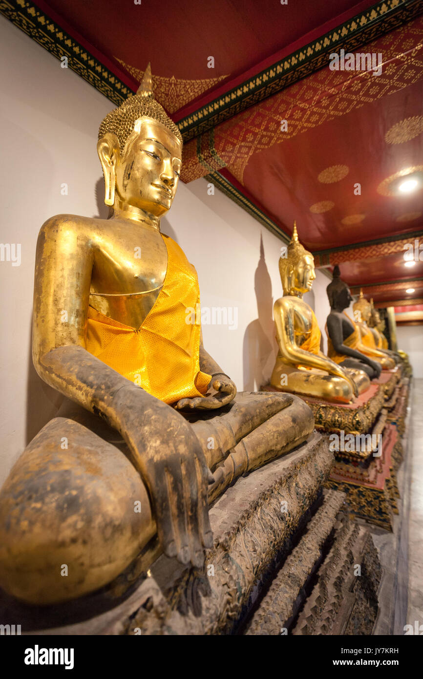 Row of praying golden sitting Buddhas at Wat Pho (Reclining Buddha Temple), Bangkok, Thailand - Stock Image