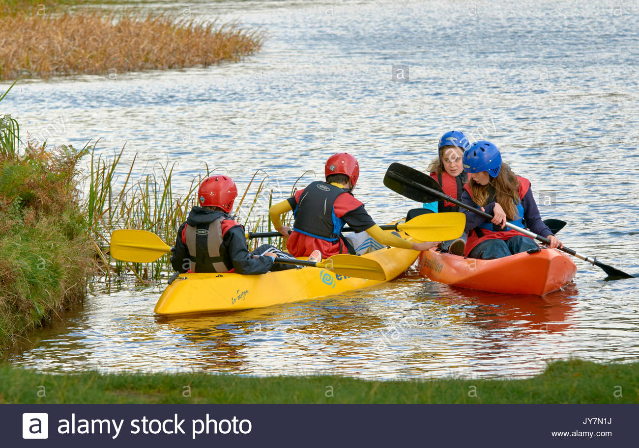 Groups of young teenagers rowing in Kayaks in Margam country park near Port Talbot South Wales UK - Stock Image