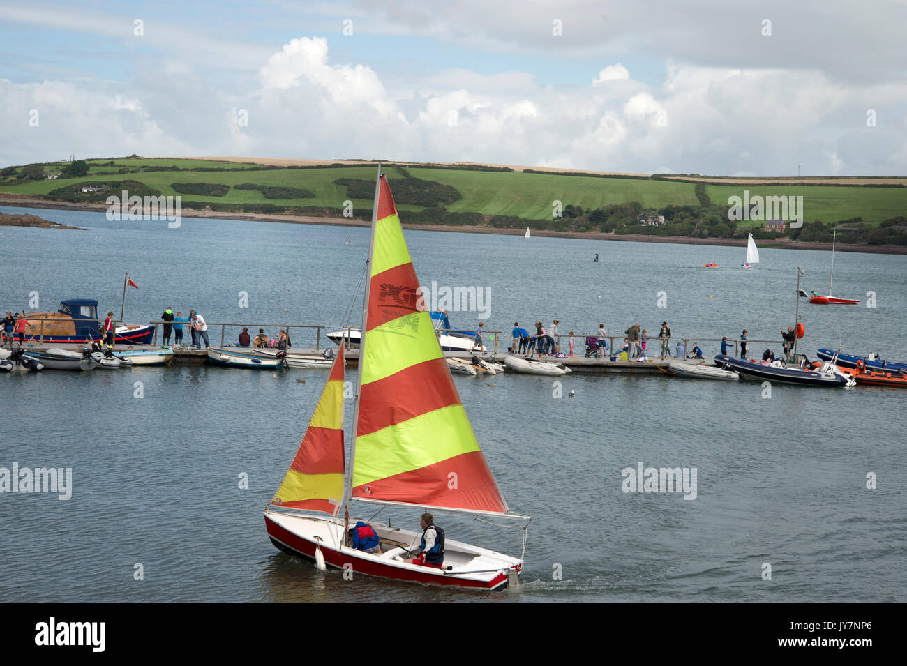 Dale, West Wales. Small dingy with stripes sails in the harbour. - Stock Image