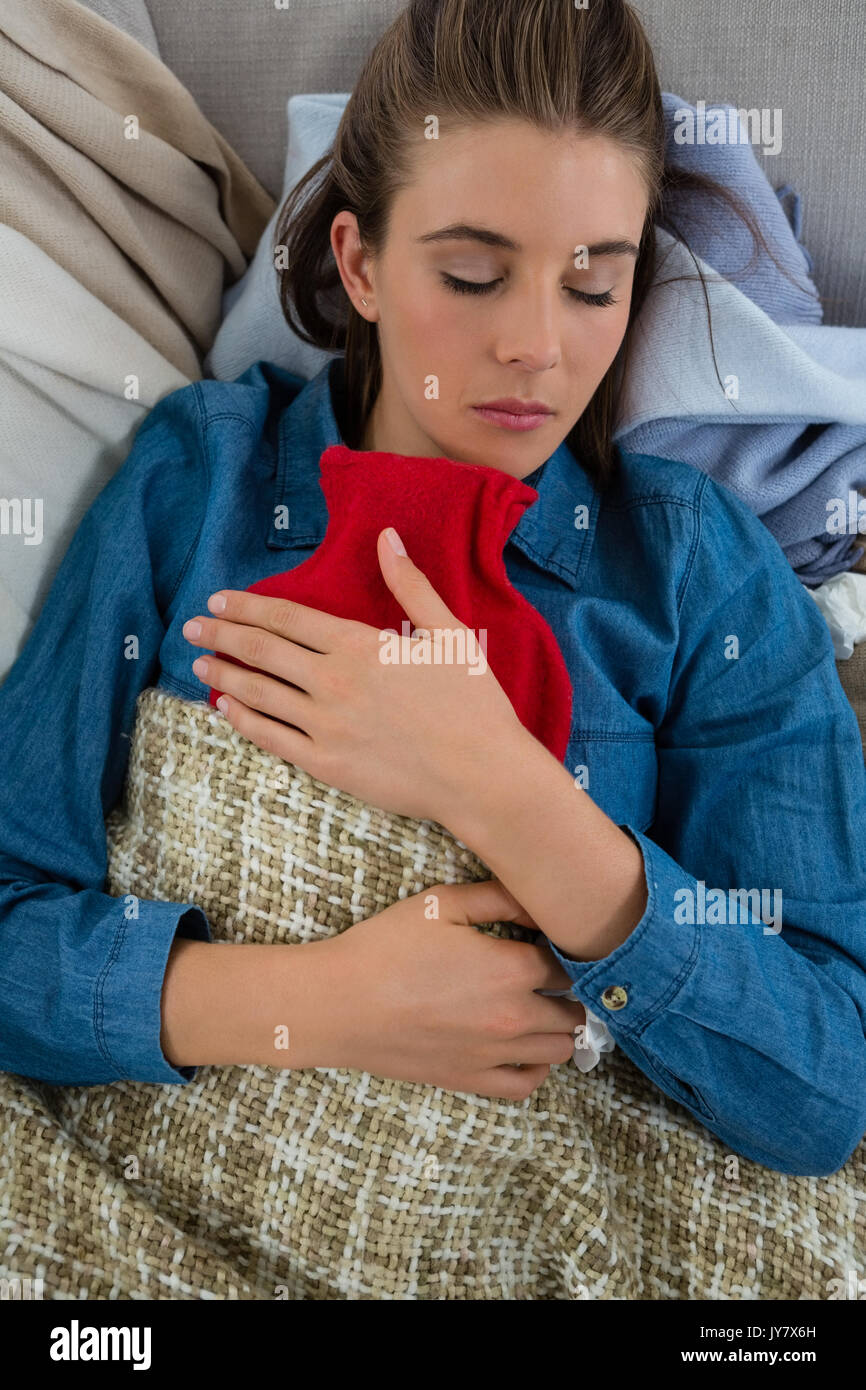 Directly above shot of woman with hot water bottle while sleeping on sofa at home - Stock Image
