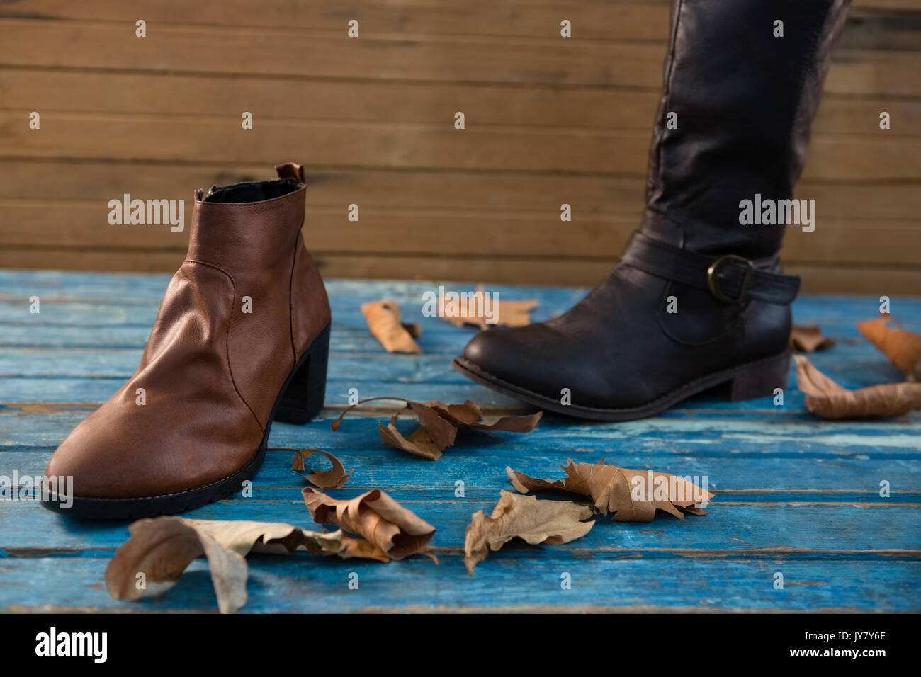 Close up boot and shoe on table by wooden wall - Stock Image
