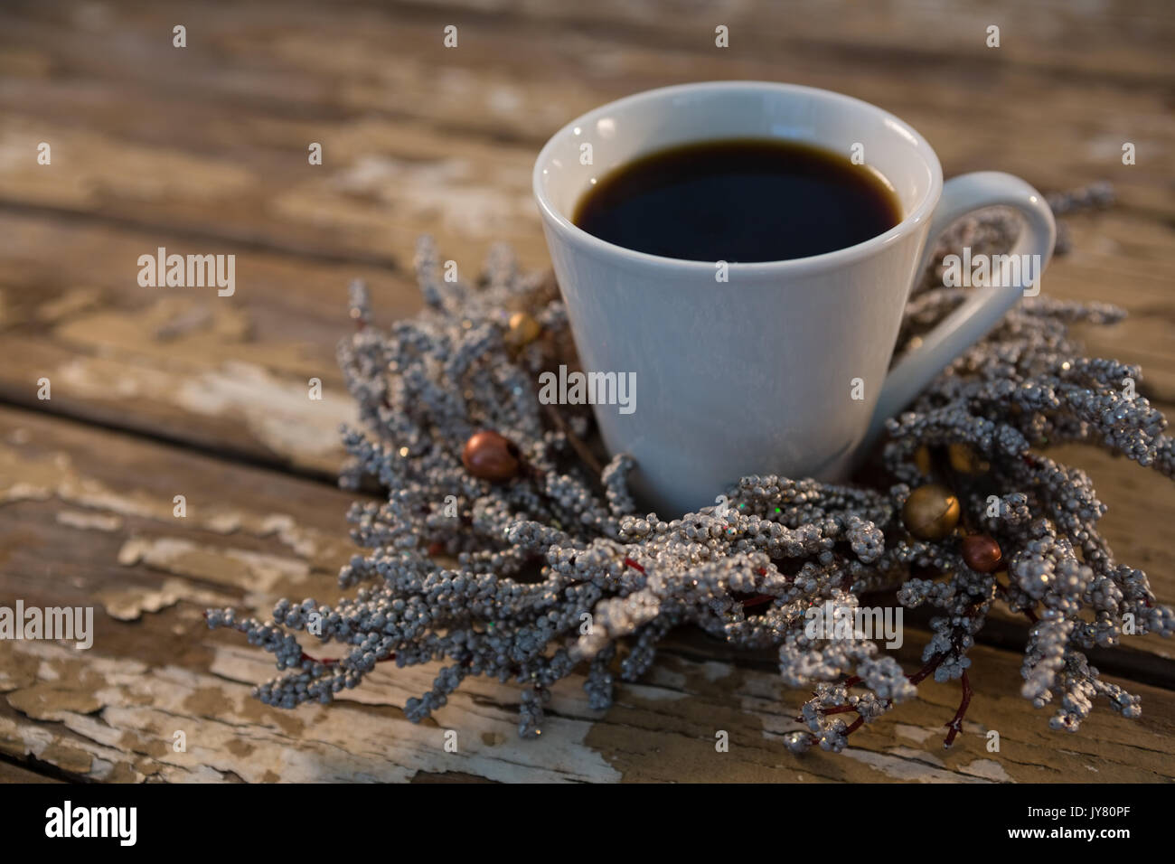 Close up of black coffee on dried plant at wooden table - Stock Image
