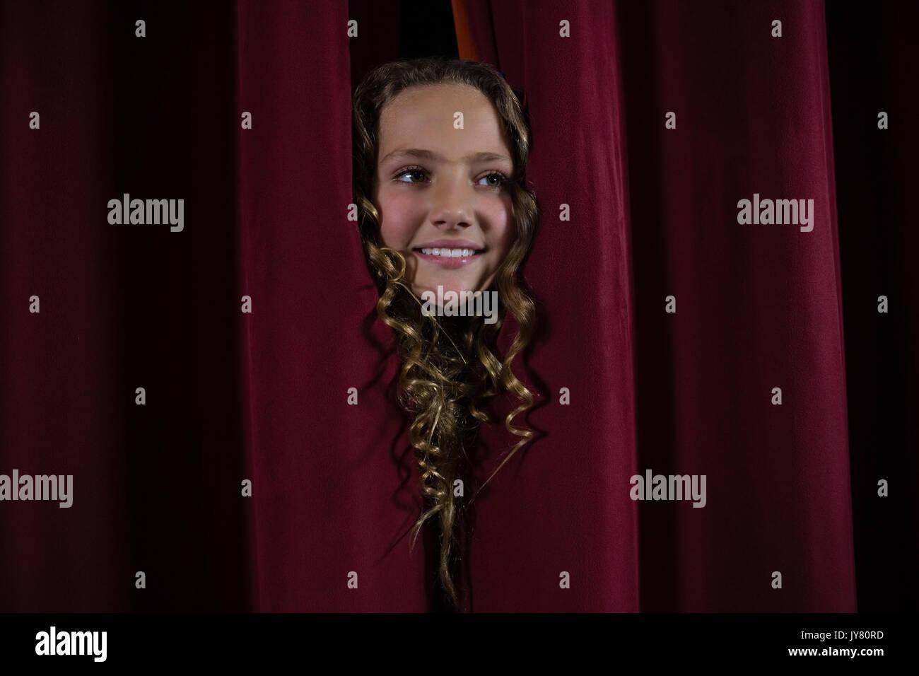 Smiling female artist peeking through the red curtain - Stock Image