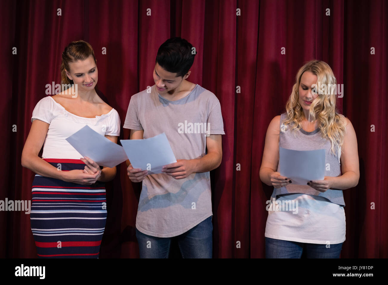 Actors reading their scripts on stage in theatre - Stock Image