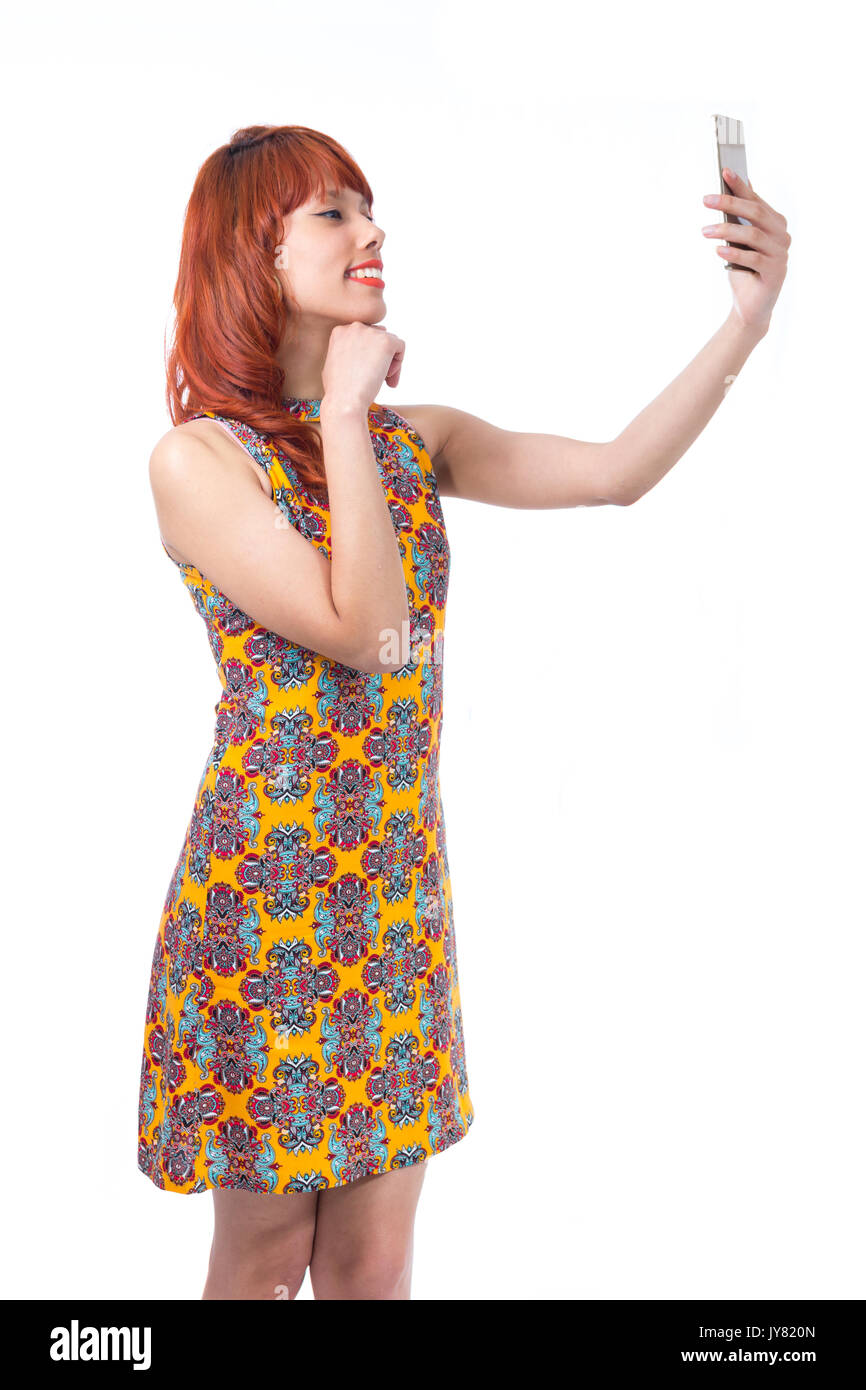 Pretty woman shoots with her cell phone. Selfie. Redhead girl wearing yellow and colorful dress. Floral pattern. Fashion and style. Summer and tropica - Stock Image