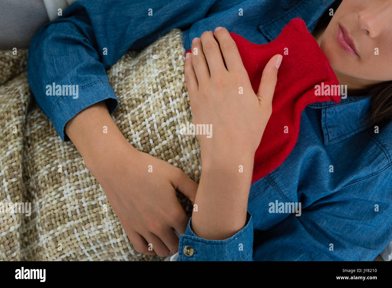 Mid section of woman with hot water bottle while sleeping on sofa at home - Stock Image