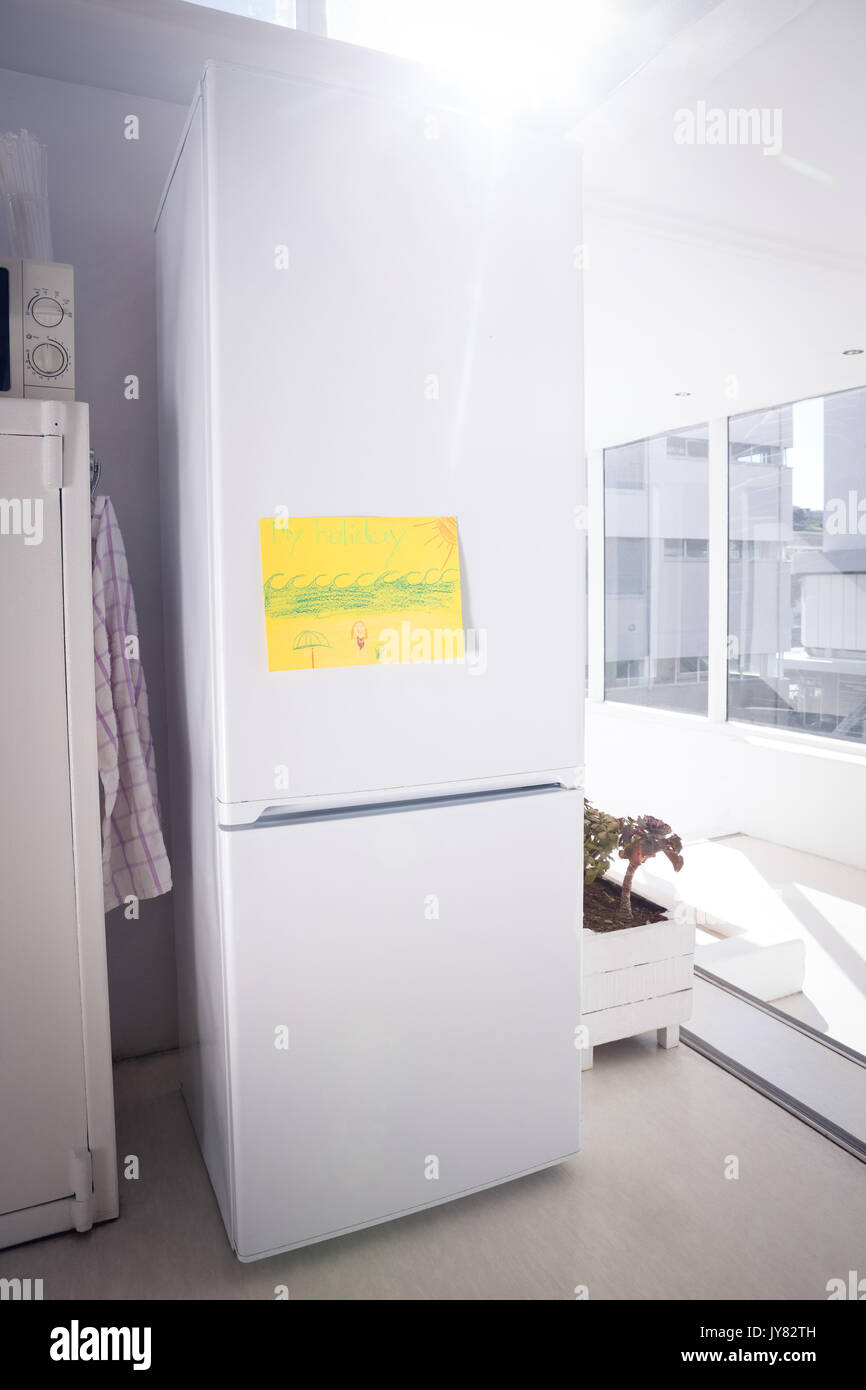 Drawing On Yellow Paper Stuck To Refrigerator By Glass