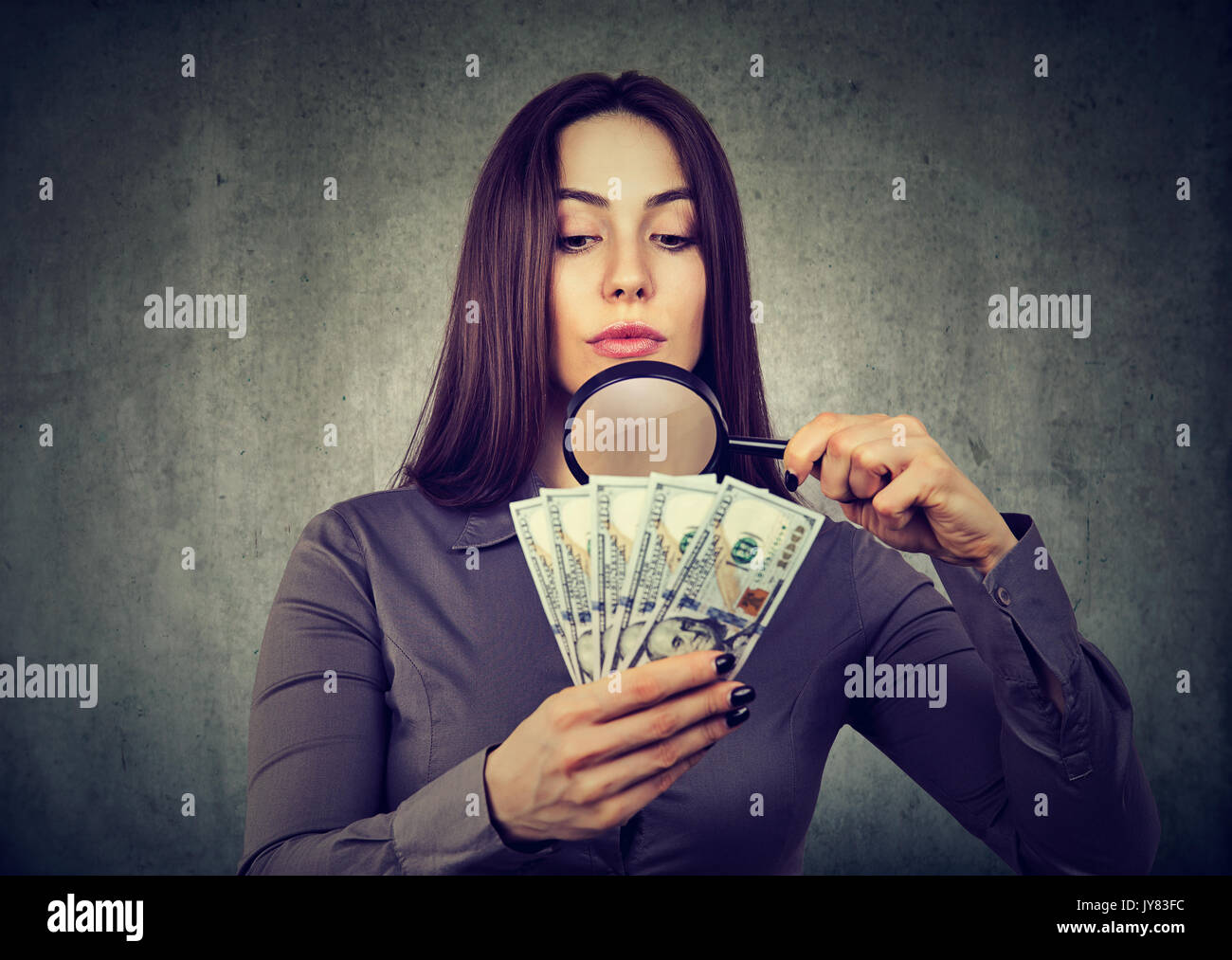 Young woman looking at one hundred dollar bills through magnifying glass - Stock Image
