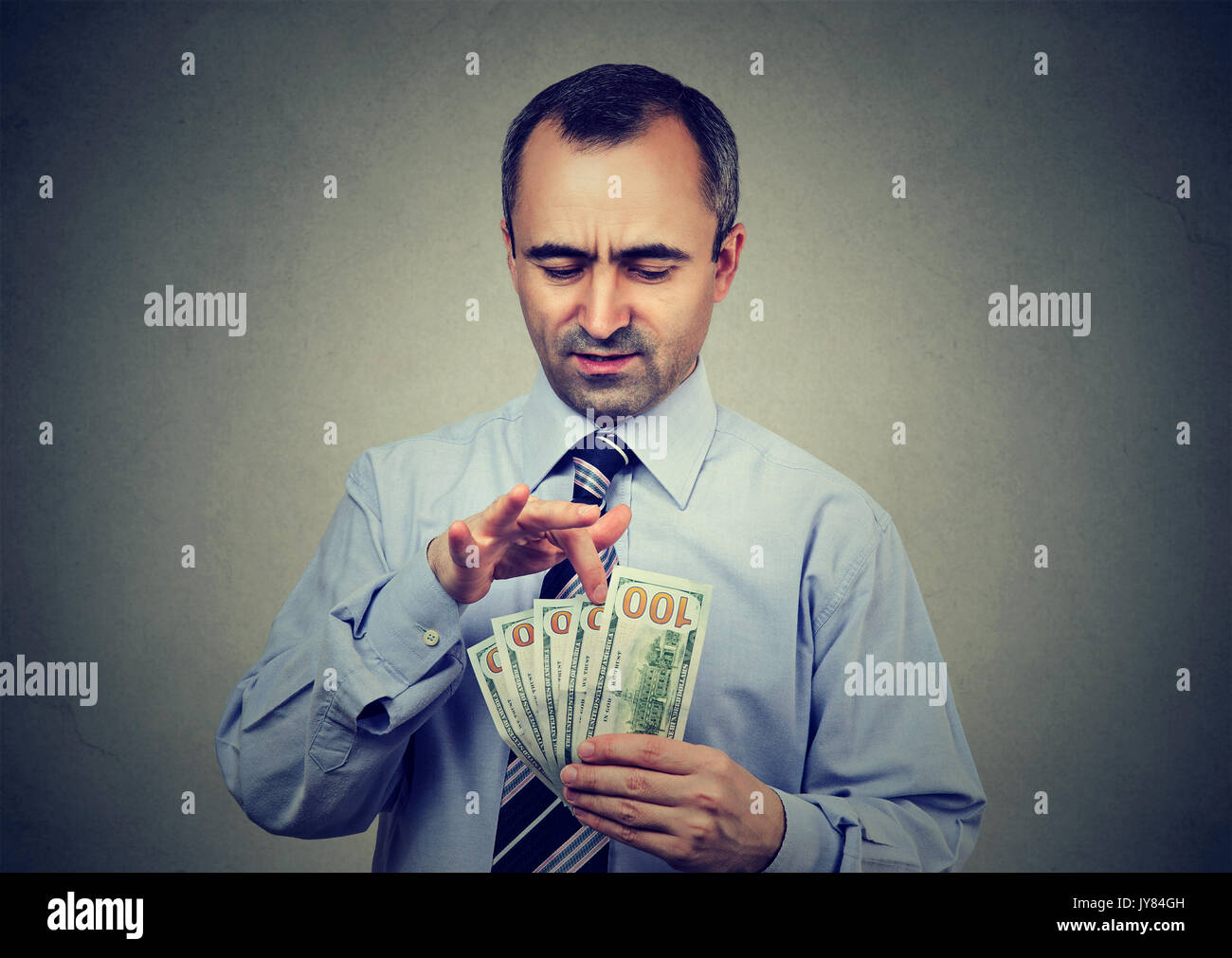 Mature business man counting money on gray background - Stock Image