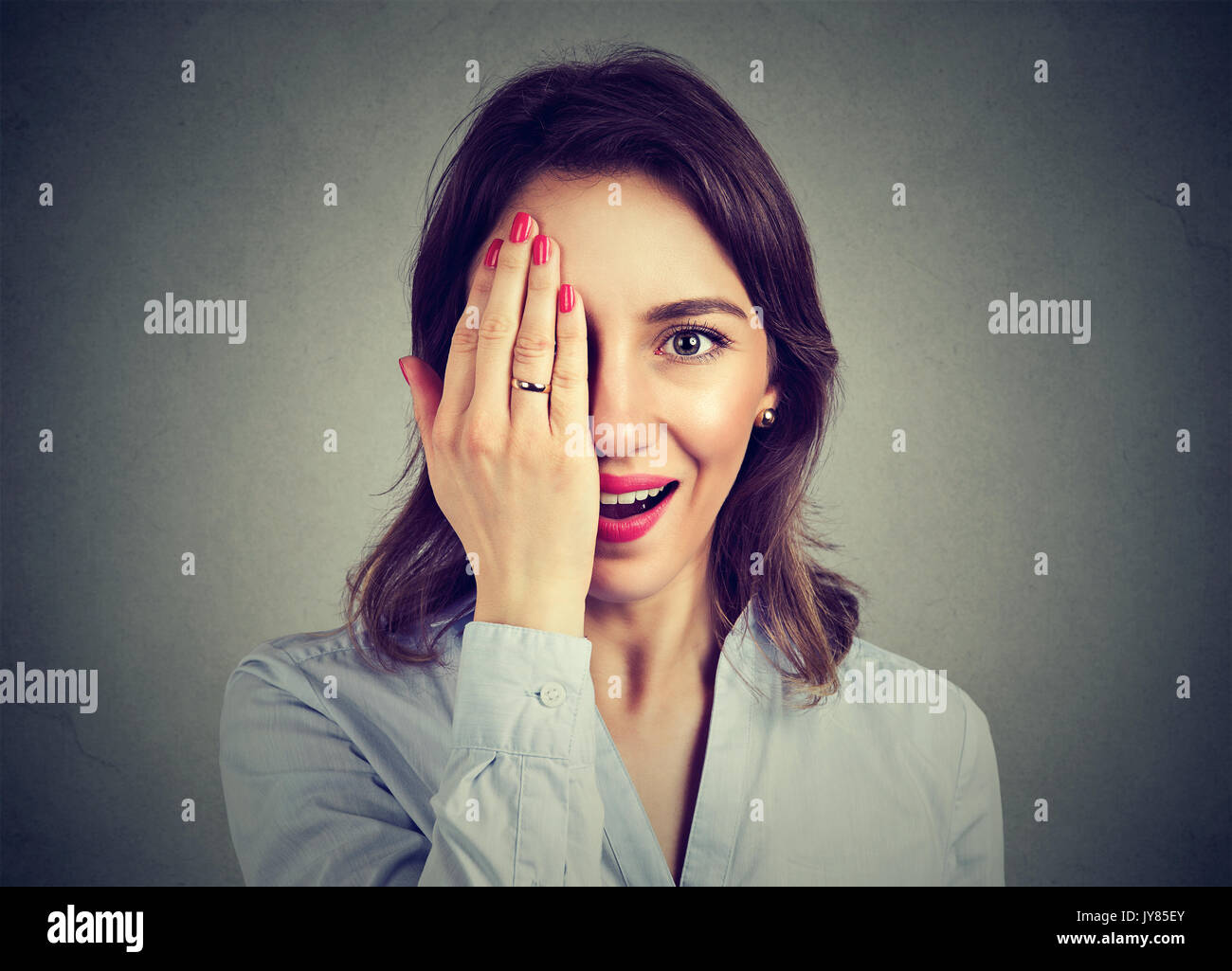 Portrait of young surprised woman covering half face with her hand - Stock Image