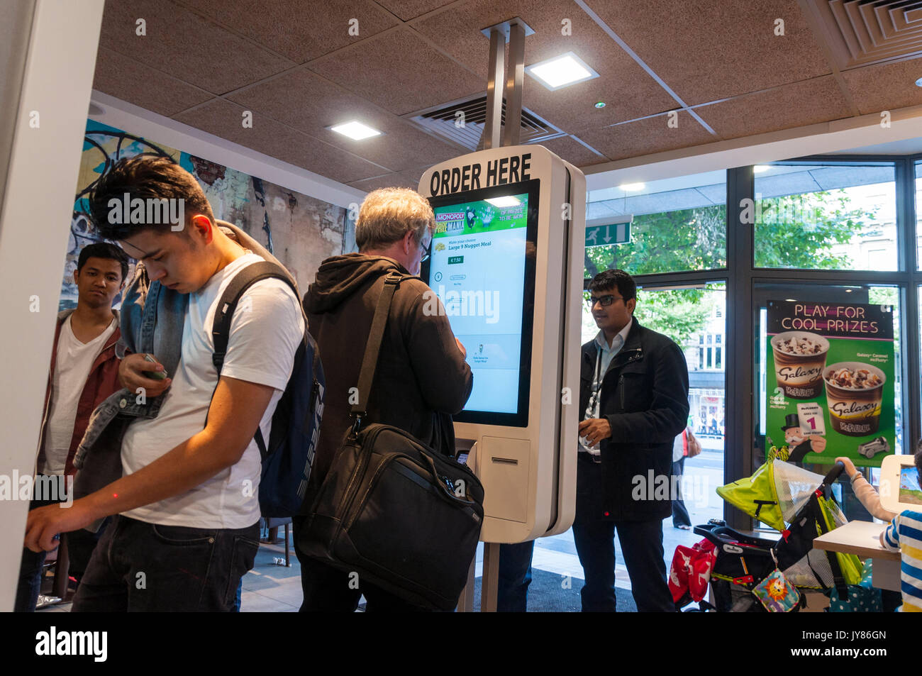 People use touch screens to order food at McDonalds on O'Connell Street in Dublin, Ireland - Stock Image