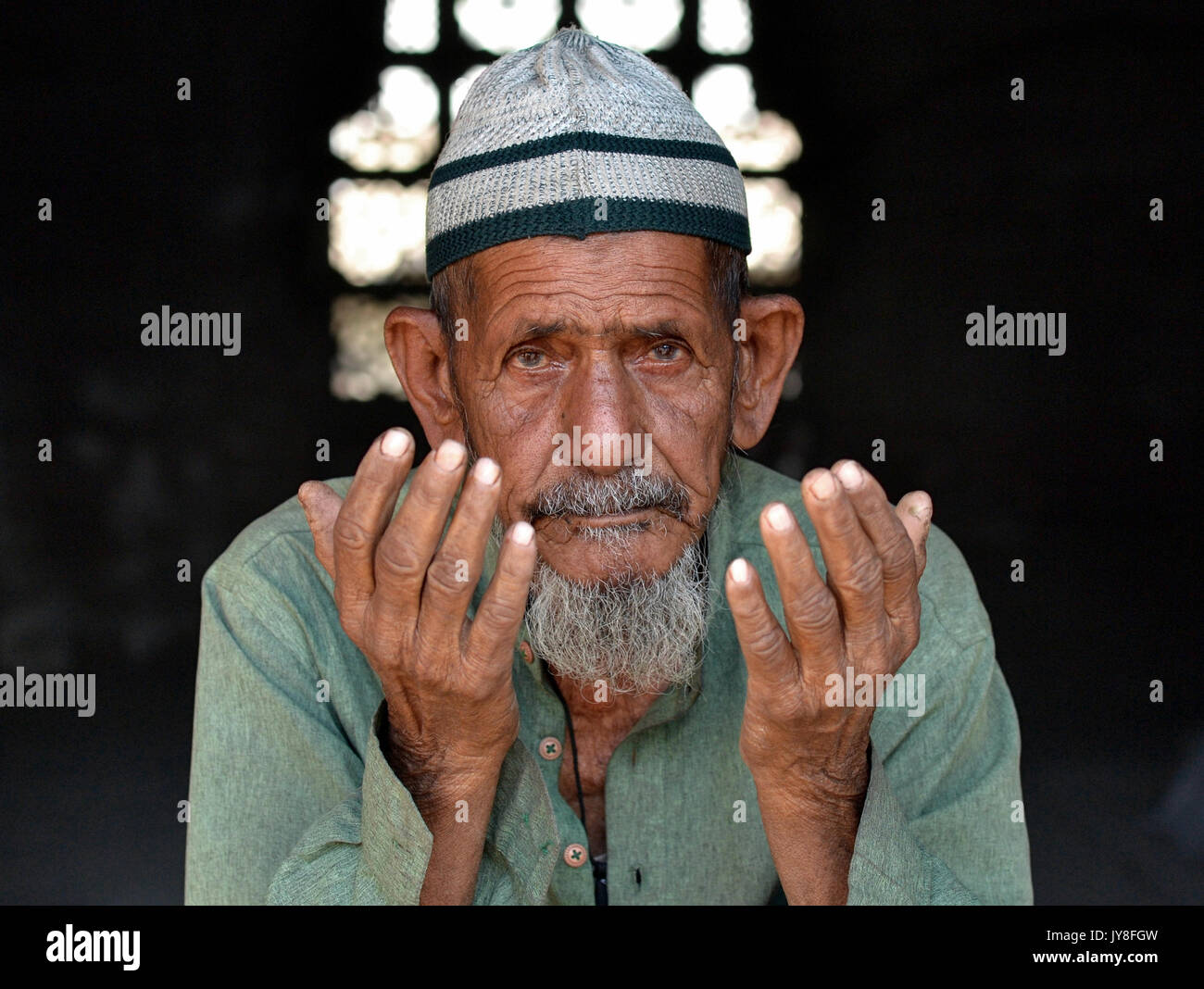 Closeup street portrait of an old Indian Muslim man with lived-in face, wearing an Islamic prayer cap (taqiyah) - Stock Image