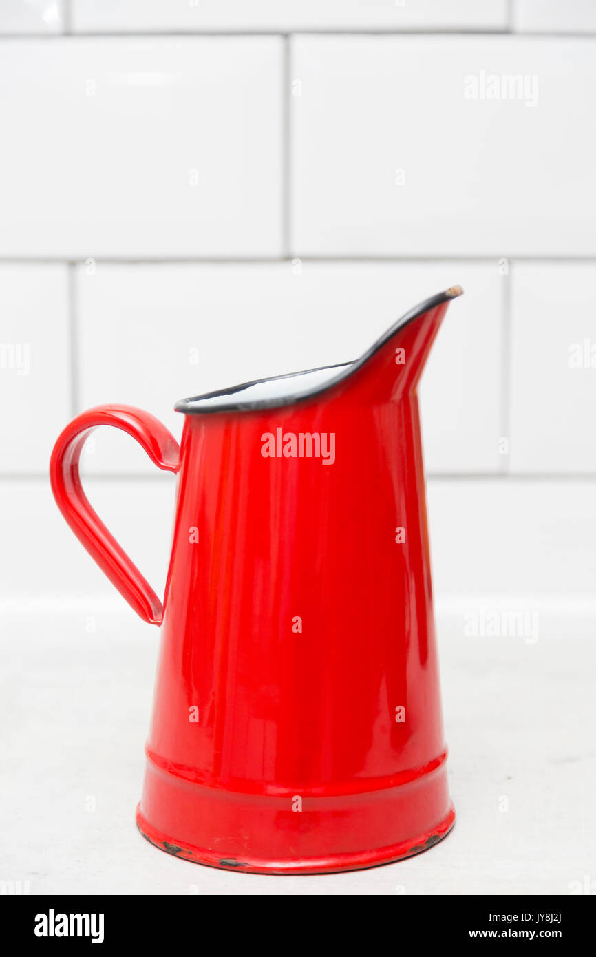 London, UK. Red and white enamel water jug against plain white tiled background. - Stock Image