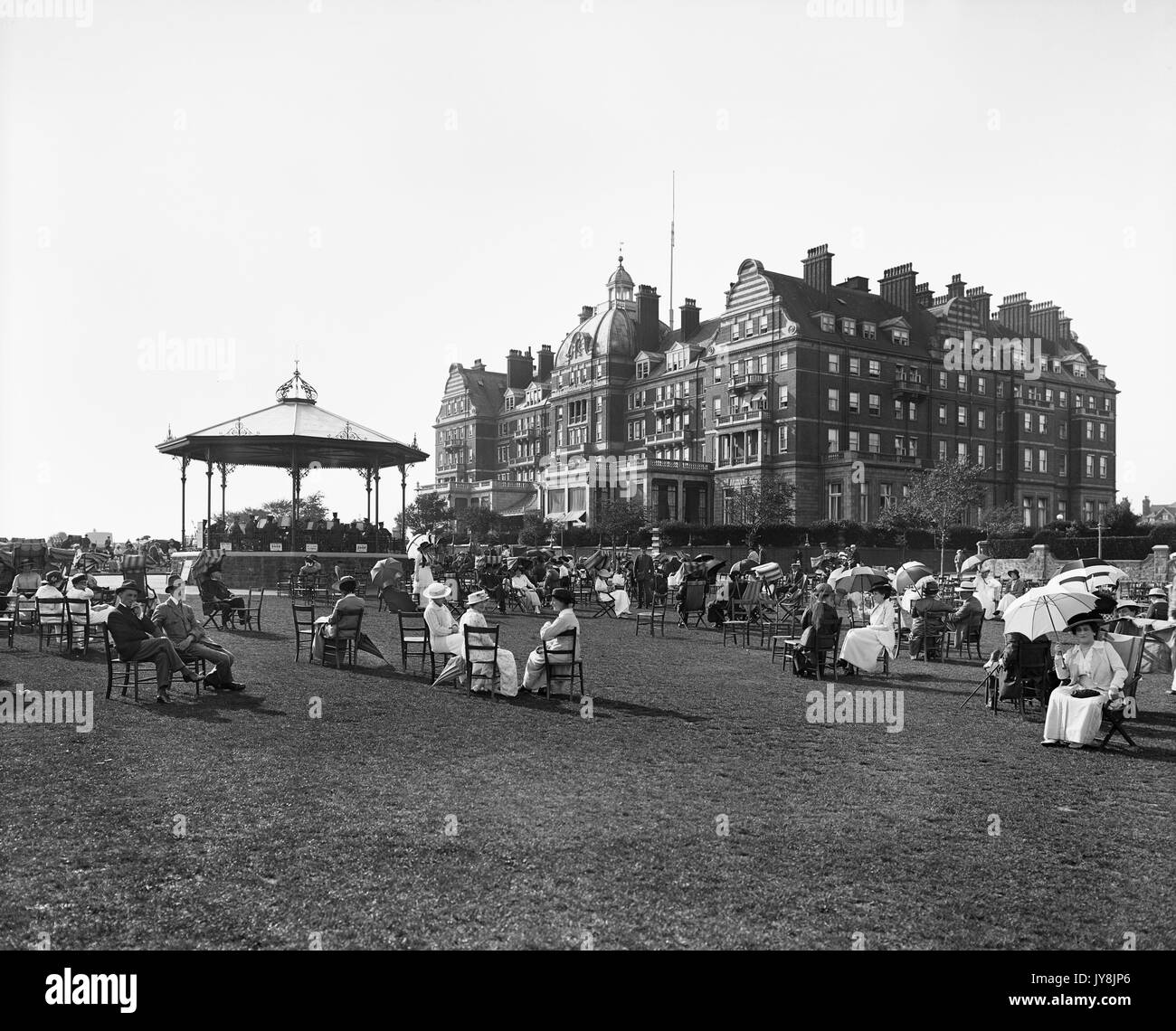 Hotel Metropole, Metropole Road East, Leas, Folkestone, Kent. View from the south-east, with people in the foreground seated around the bandstand on The Leas. Photographed in August 1915 by Henry Bedford Lemere. - Stock Image