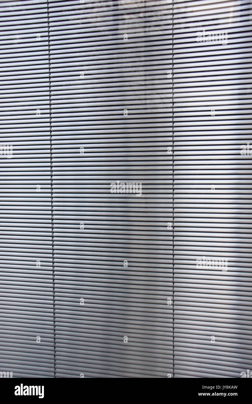 metal blinds behind a window, window blinds and shades window coverings, horizontal slats of metal, awnings, window Stock Photo