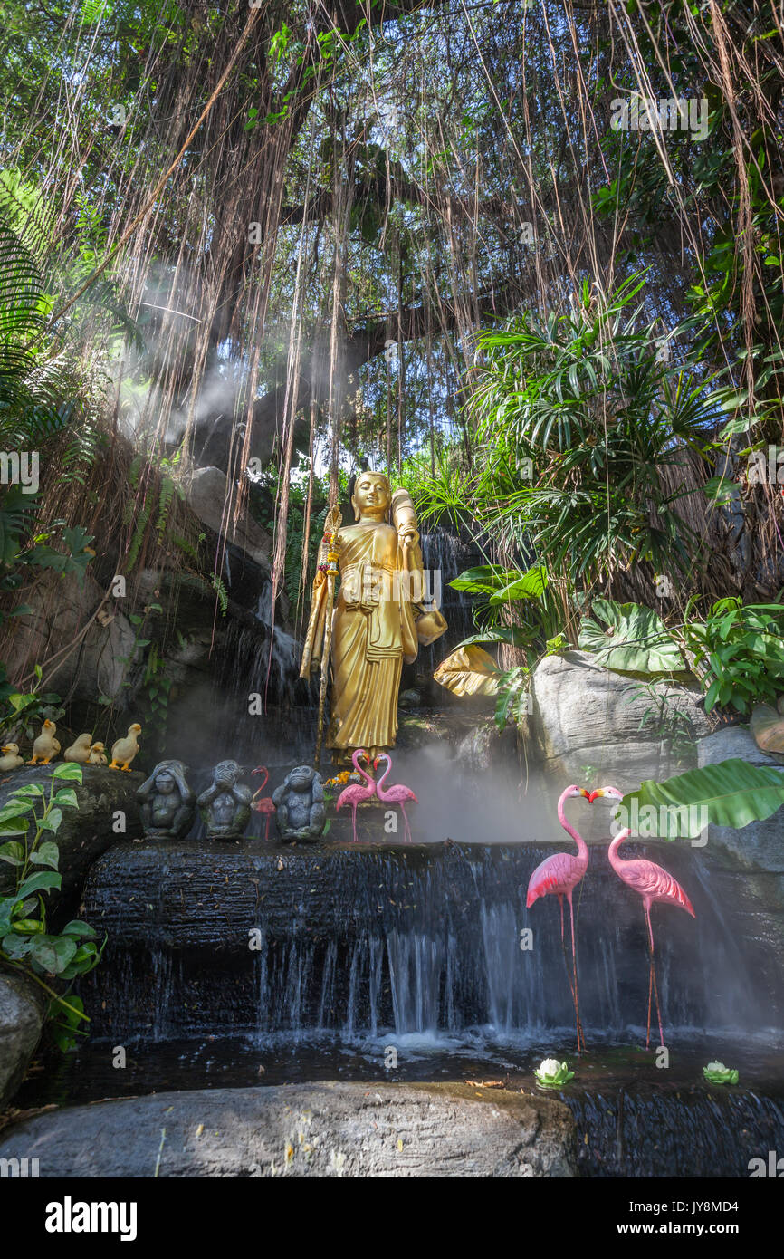 Golden Buddha statue in the tropical garden with waterfall in Wat Saket Golden Mountain Temple, Bangkok, Thailand - Stock Image