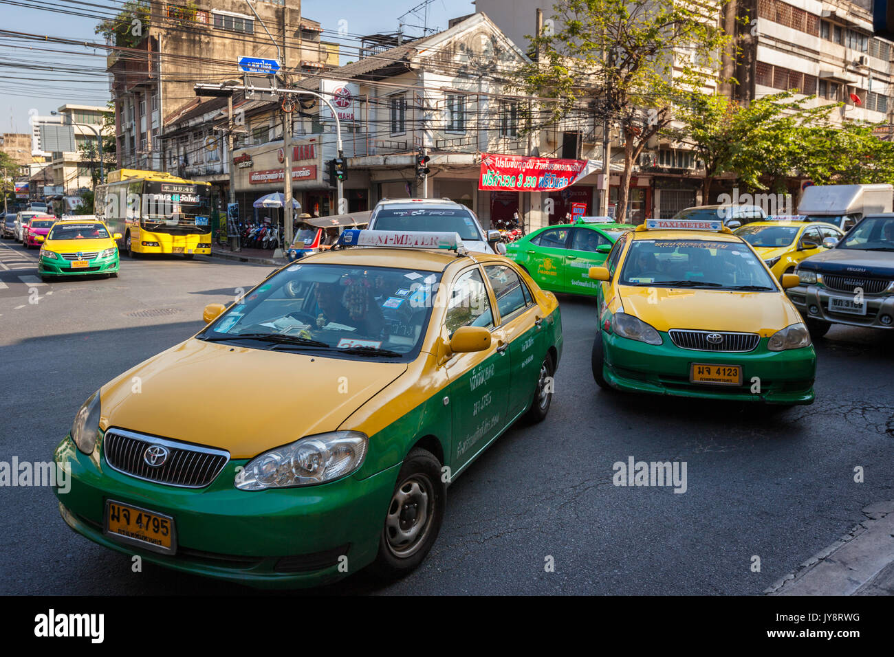 Traditional thai green yellow metered taxis around Khao San Road, Bangkok, Thailand - Stock Image