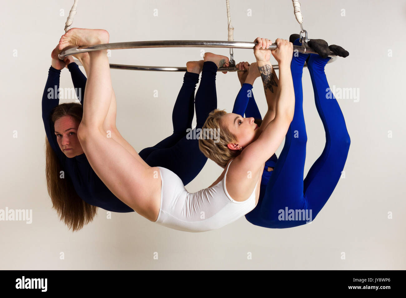 Young woman`s trio doing som acrobatic tricks on aerial luster - Stock Image
