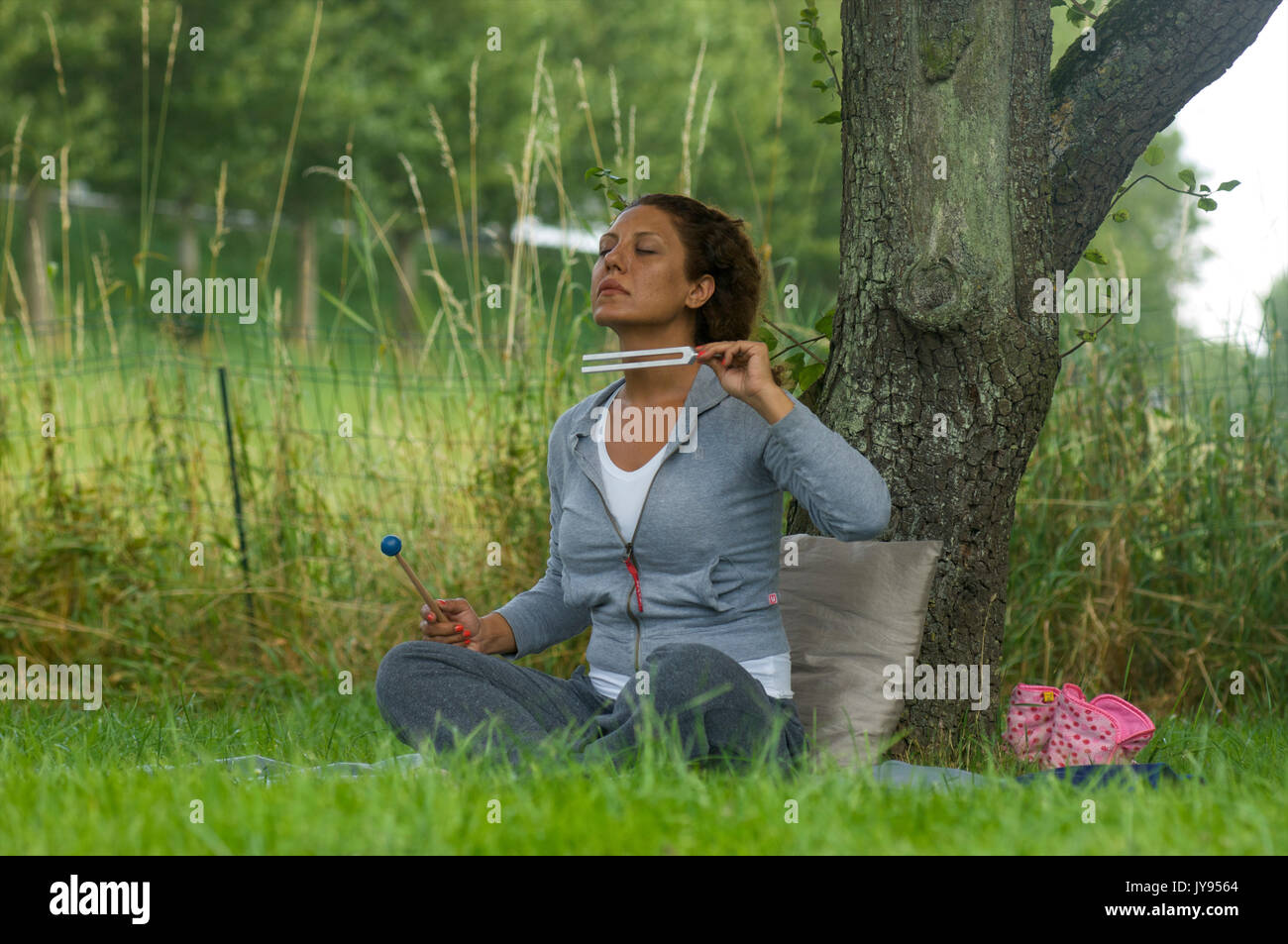 Woman working on her crown chakra and third eye chakra with a tuning fork to create balance through sound and vibration - Stock Image