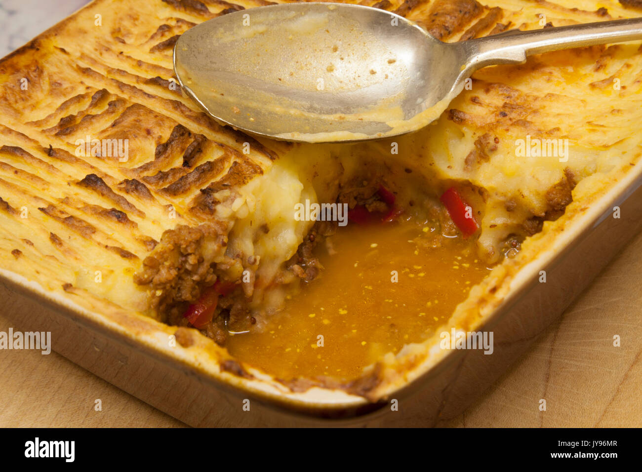 Homemade cottage pie with an Italian style twist hot out of the oven with a portion missing, made with minced beef, red peppers and leeks. - Stock Image