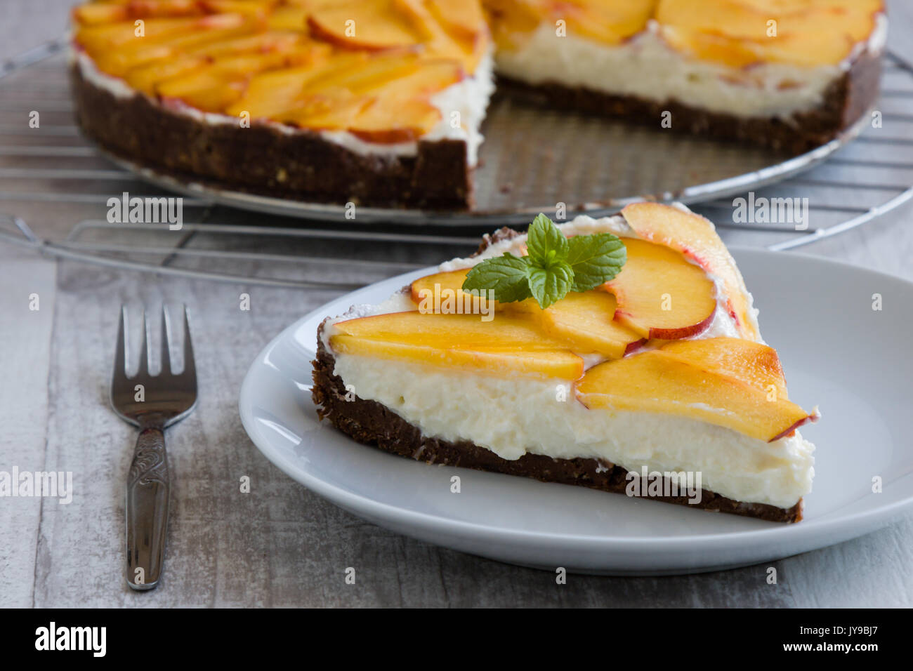 cheesecake dessert with thin slices of peach - Stock Image