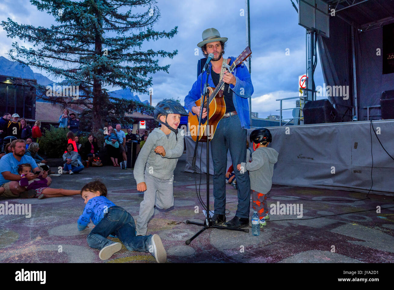 Langhorne Slim performs while kids play around him at Canmore Folk Music Festival, Canmore, Alberta, Canada Stock Photo
