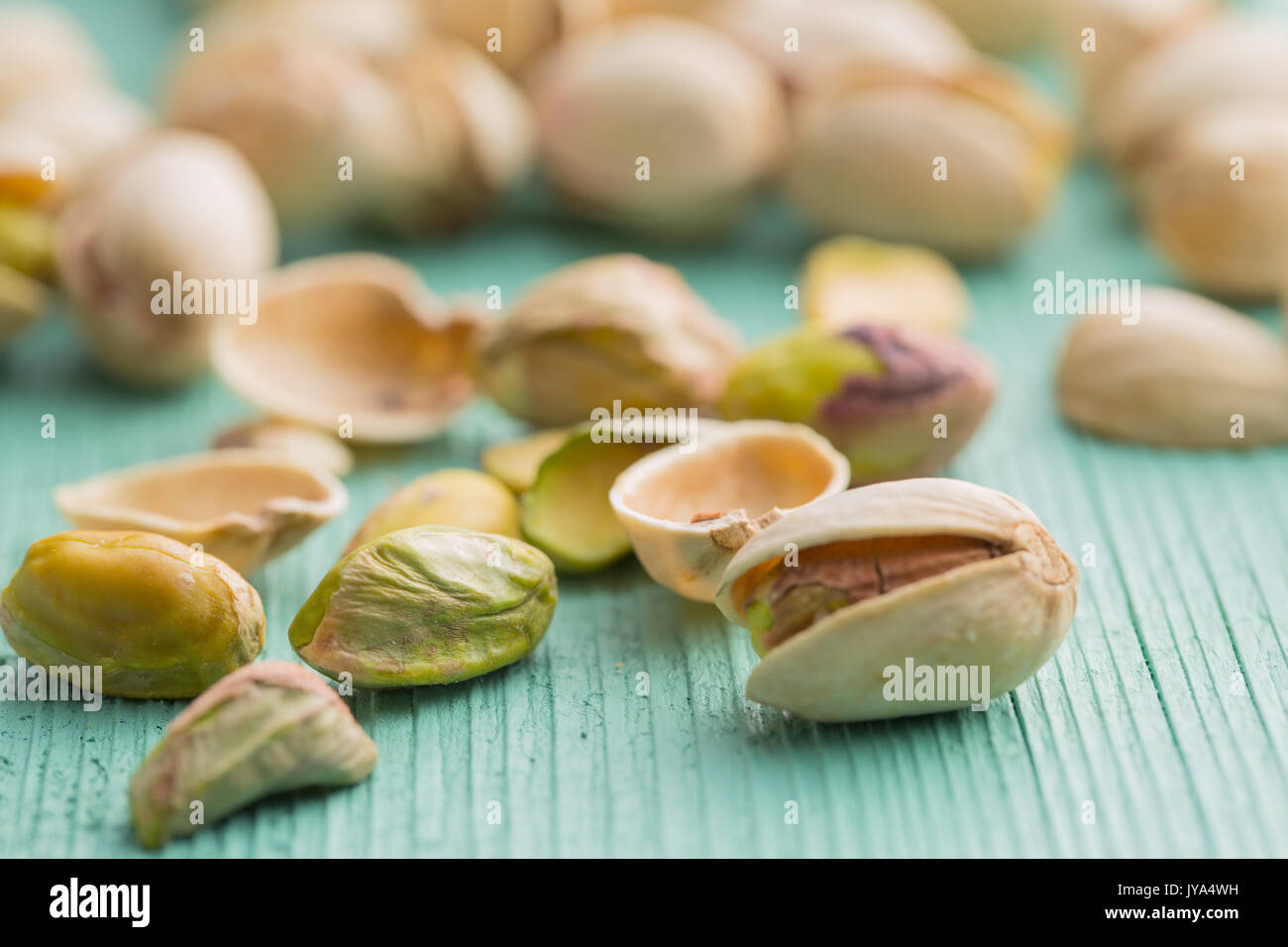 Dried pistachio nuts. On green wooden table.  Pistachio kernel. - Stock Image