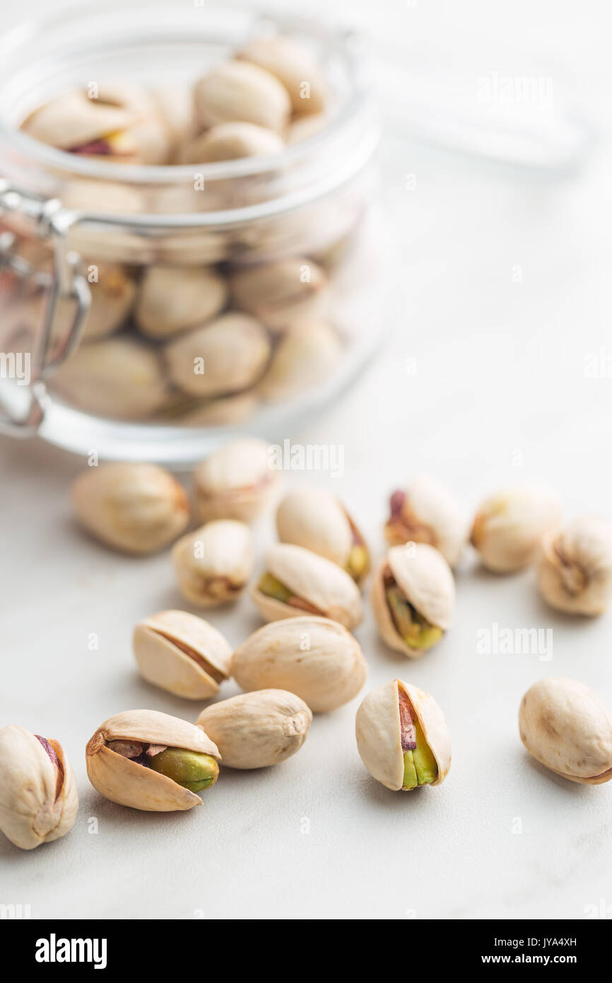 Dried pistachio nuts in jar on kitchen table. Pistachio kernel. - Stock Image